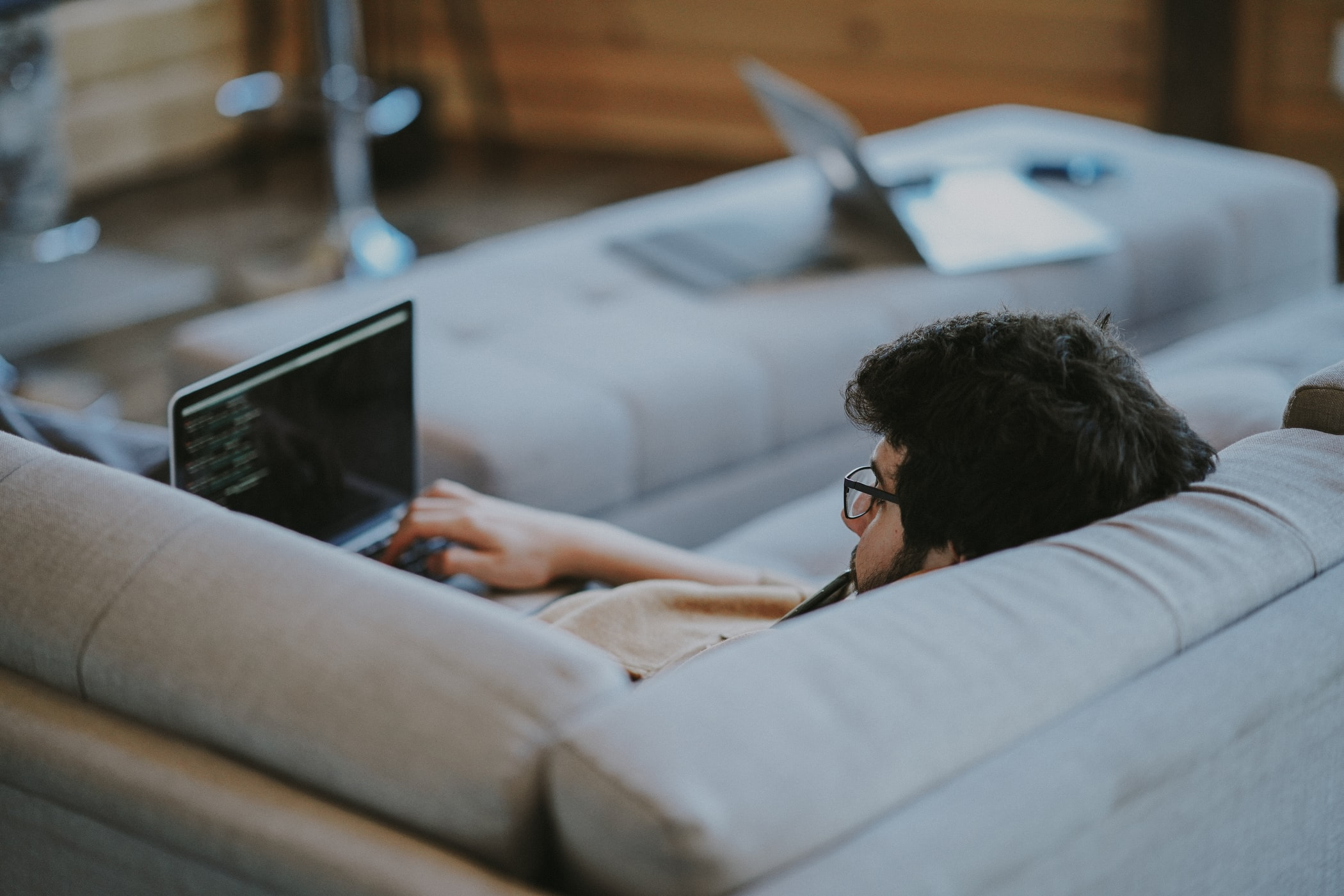 Low code developer sitting in his couch working